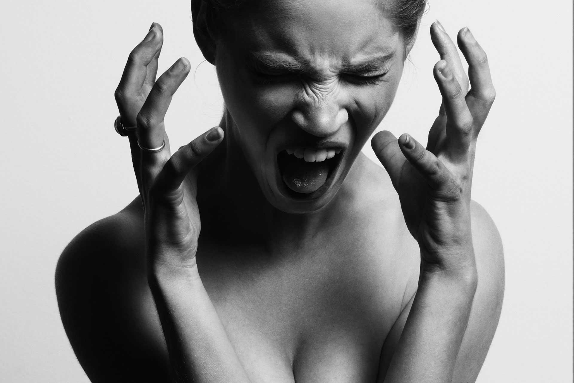 Frau schreit mit geschlossenen Augen, hält Hände auf Kopfhöhe